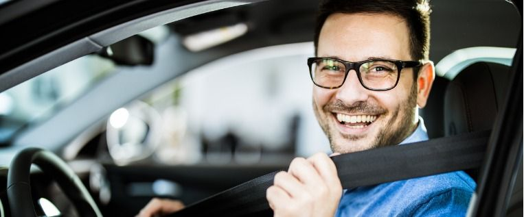 happy-businessman-fastening-seatbelt-before-his-trip-by-car-picture-id1156320690