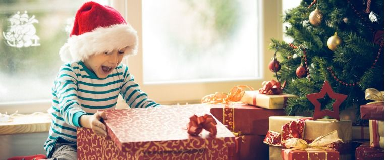 surprised-little-boy-opening-christmas-present-picture-id528107199
